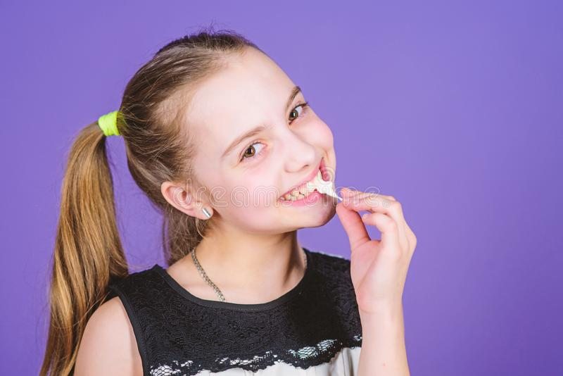 Hungry kid. Incorrigible sweet tooth. Girl smiling face holds sweet marshmallows in hand violet background. Sweet tooth. Concept. Kid girl with long hair likes stock photography