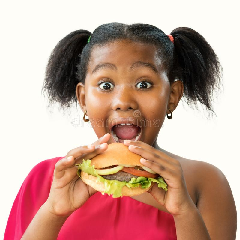 Hungry little african girl about to eat hamburger. stock photos