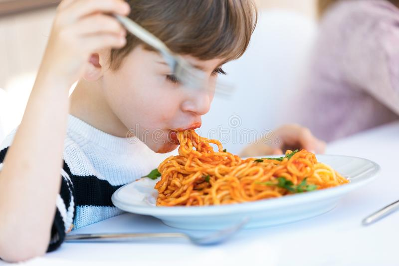 Hungry little boy eating spaghetti with tomato sauce in the kitchen at home stock photo