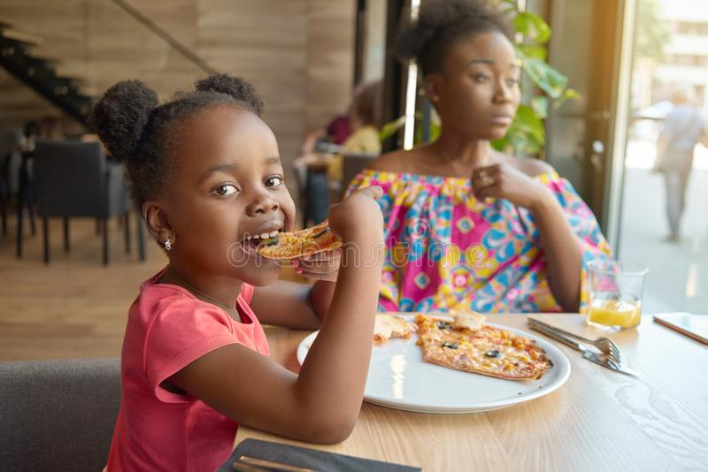 Hungry little girl eating pizza sitting near her mother in cafe. Happy, having good mood, wonderful time together, lovely family. Other clients sitting in cafe royalty free stock photography