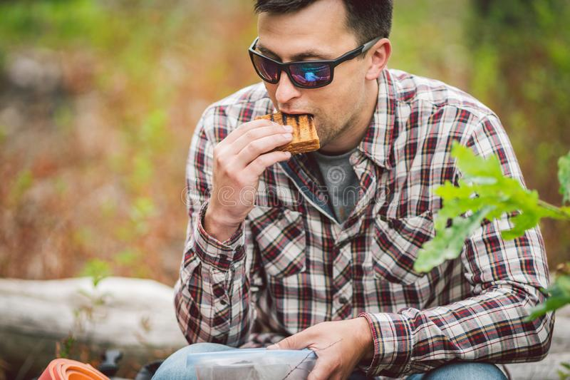 Hungry man eating. Sandwich outdoors. hiker eating sandwich sitting in forest. tourist eat snack food. Hiker take break with time. For food. Caucasian guy royalty free stock photography