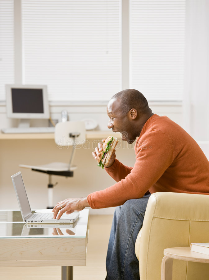 Hungry man eating a sandwich and typing on laptop stock images