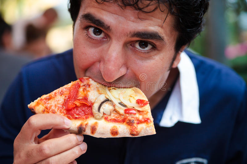 Hungry man eating slice of pizza stock image