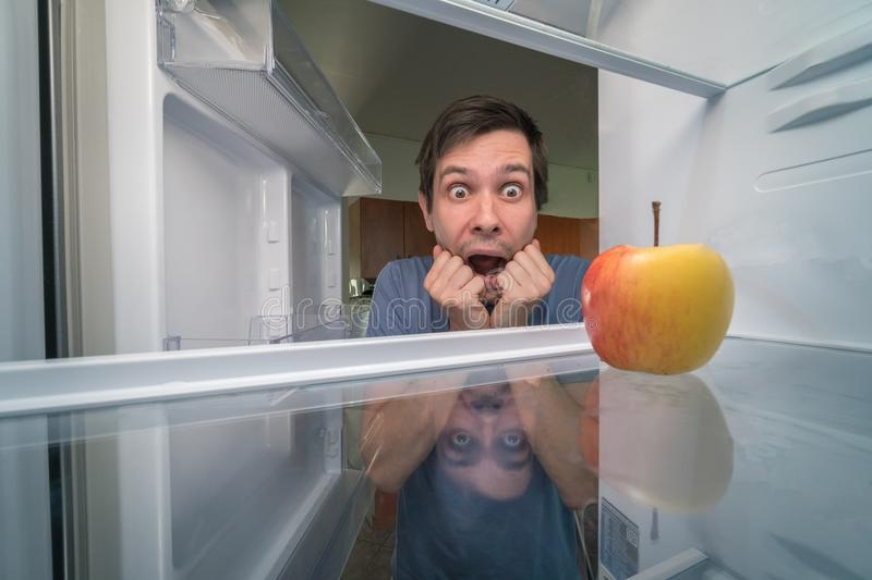 Hungry man is looking for food in fridge and is shocked. Only apple is inside empty fridge.  royalty free stock photo