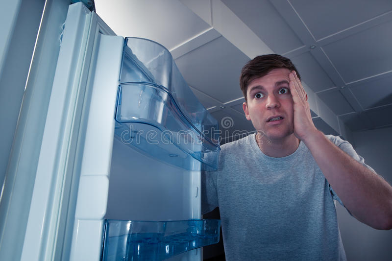 Hungry man looking in refrigerator royalty free stock images