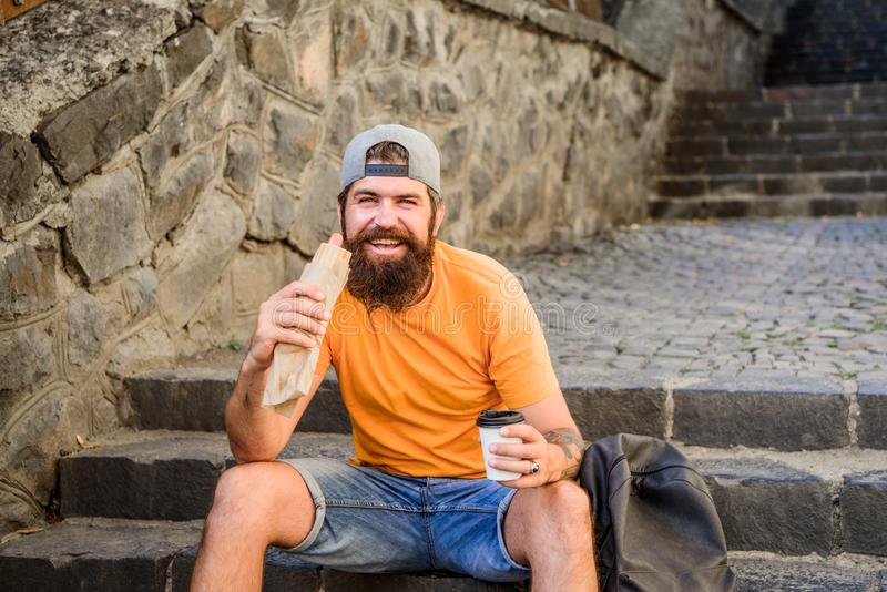 Hungry man snack. Junk food. Guy eating hot dog. Man bearded enjoy quick snack. Street food so good. Urban lifestyle and royalty free stock photo
