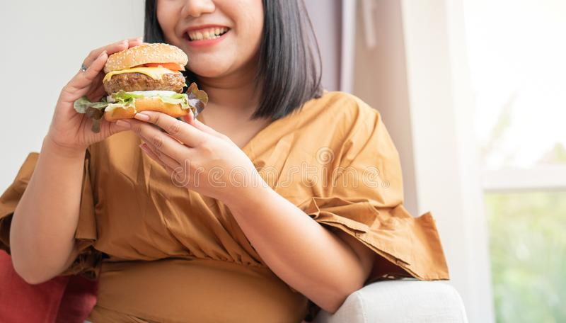 Hungry overweight woman smiling and holding hamburger and sitting in the living room, her very happy and enjoy to eat fast food. C royalty free stock images