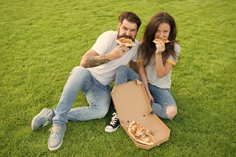 Hungry people. Simple happiness. Cheat meal. Couple eating pizza relaxing on green lawn. Fast food delivery. Bearded man stock image