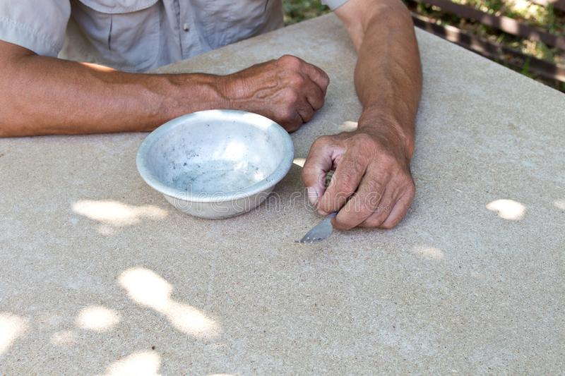 Hungry. Poor old man& x27;s hands an empty bowl. Selective focus. Poverty in retirement. Alms royalty free stock image