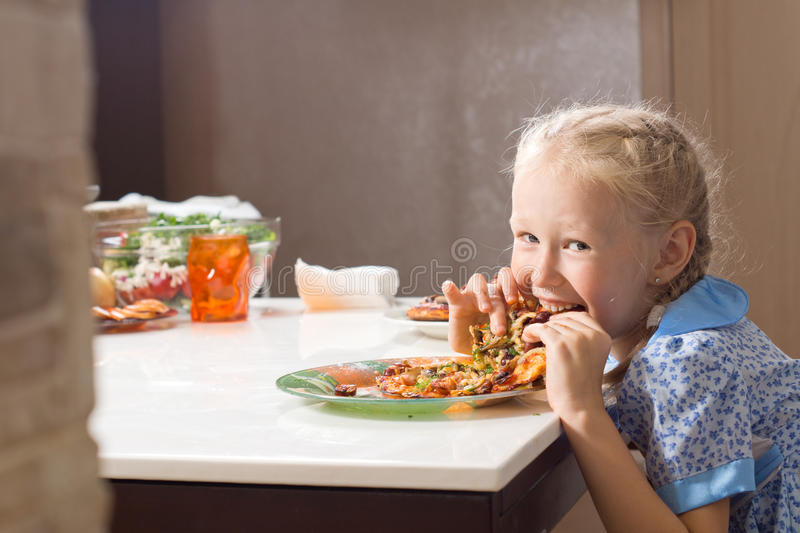 Hungry pretty little girl devouring homemade pizza. Looking up from taking a mouthful with a cheeky smile of enjoyment stock photo