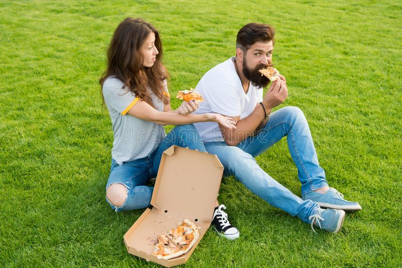 Hungry students sharing food. Pure enjoyment. Couple eating pizza relaxing on green lawn. Fast food delivery. Bearded stock image