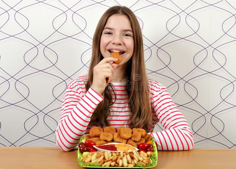 Teenage girl eats chicken nuggets royalty free stock photography