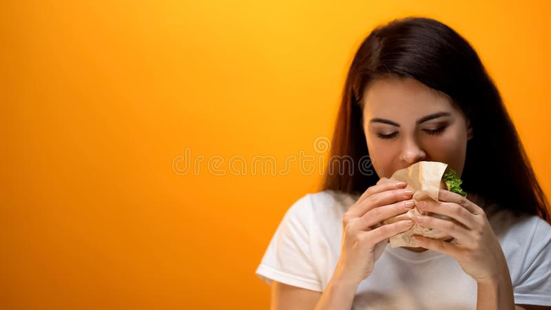 Hungry woman eating hamburger, addiction to unhealthy nutrition, fast food stock photography