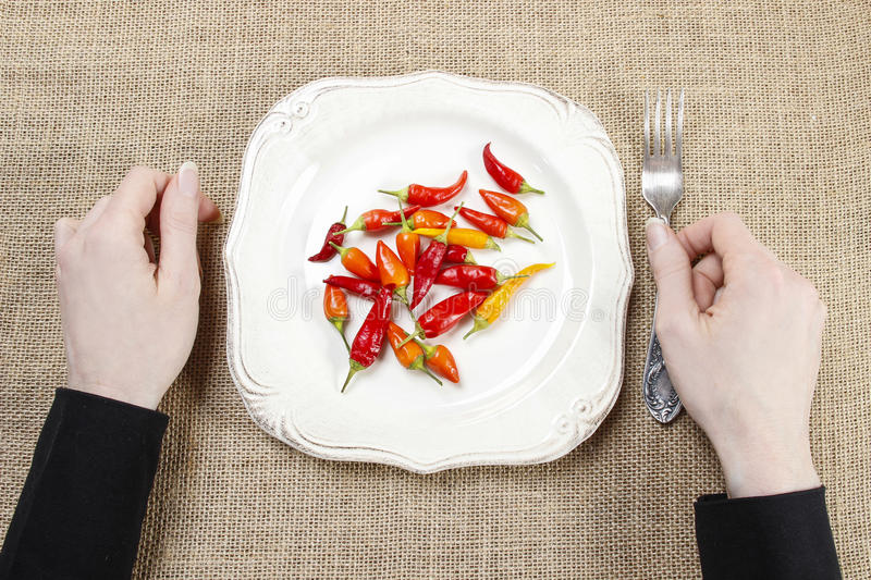 Hungry woman eating red hot chili peppers. Symbol of adapting to stock image