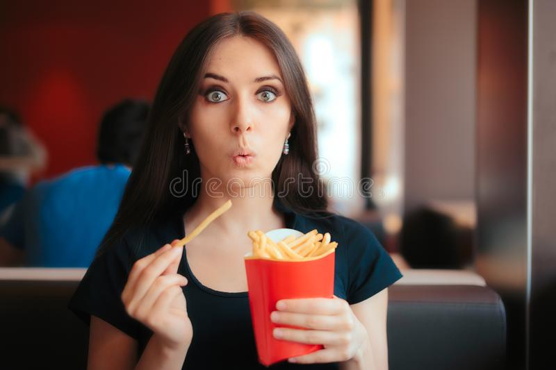 Funny Girl Eating Fries in French Fast Food Restaurant. Hungry woman having a quick unhealthy snack at a dinner royalty free stock photography