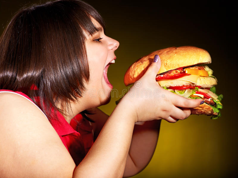 Hungry woman holding hamburger. Overweight hungry woman eating hamburger royalty free stock photo