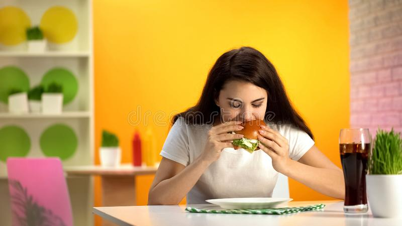 Hungry young lady eating tasty cheeseburger in cafe, soft drink glass on table royalty free stock photos