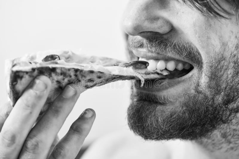 Hungry young man in underwear sits at home on a bed with a pizza box. Break diet concept. Food delivery service. Home. Pizza stock photo