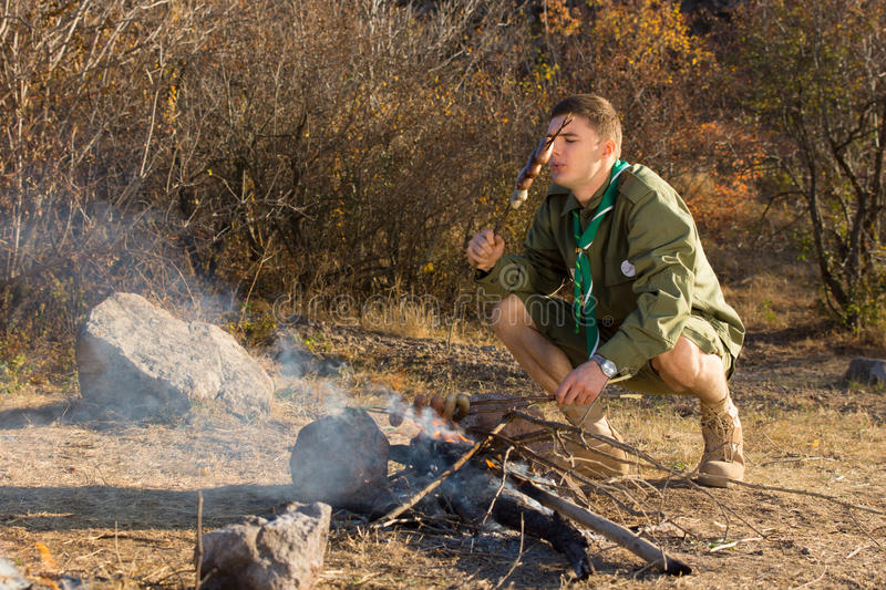 Hungry young scout cooking sausages royalty free stock photos