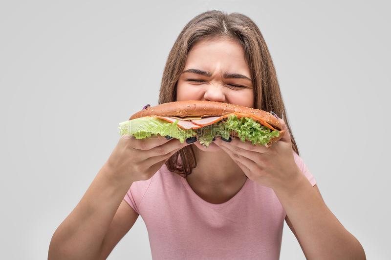Hungry young woman bite burger. She devour it. Isolated on grey background. royalty free stock images