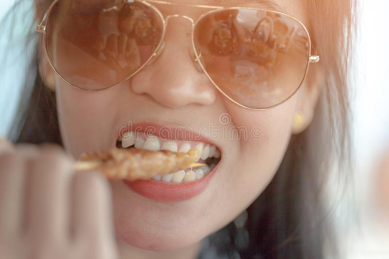 Hungry young woman eating roast pork.selective focus. royalty free stock image