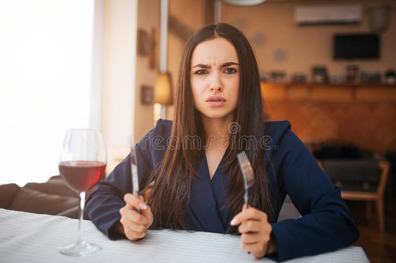 Hungry young woman look on camera. She is angry. Model hold fork and knife in hands. She sit at table in restaurant. stock image