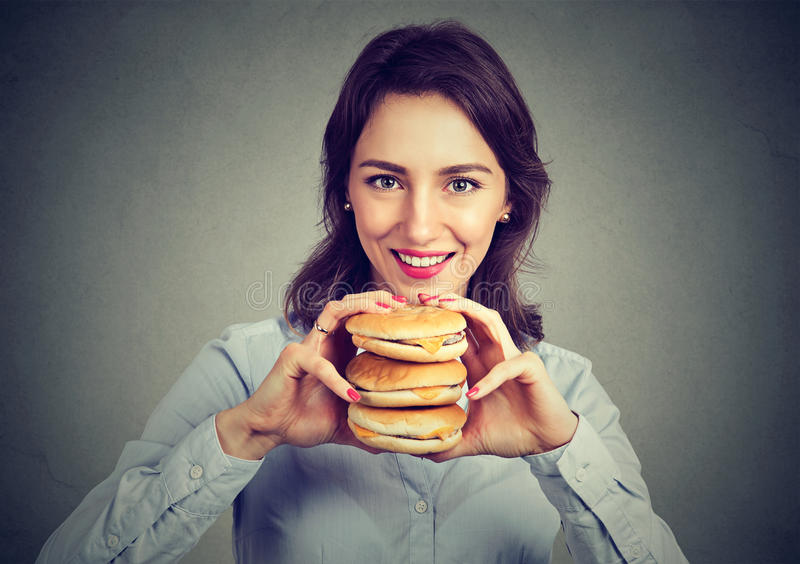 Hungry young woman with a tasty triple burger. Hungry woman with a tasty triple burger stock images