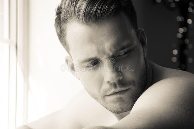 Hunky mięśniowy, seksowny bez koszuli mężczyzna z definiującym abs, i mięśni spojrzenia z okno obraz royalty free