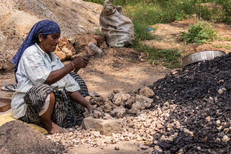 Woman crushes limeston in Hunsur, Karnataka, India. Hunsur, Karnataka, India - November 1, 2013: Seated woman with head scarf crushes limestone with heavy stock photo