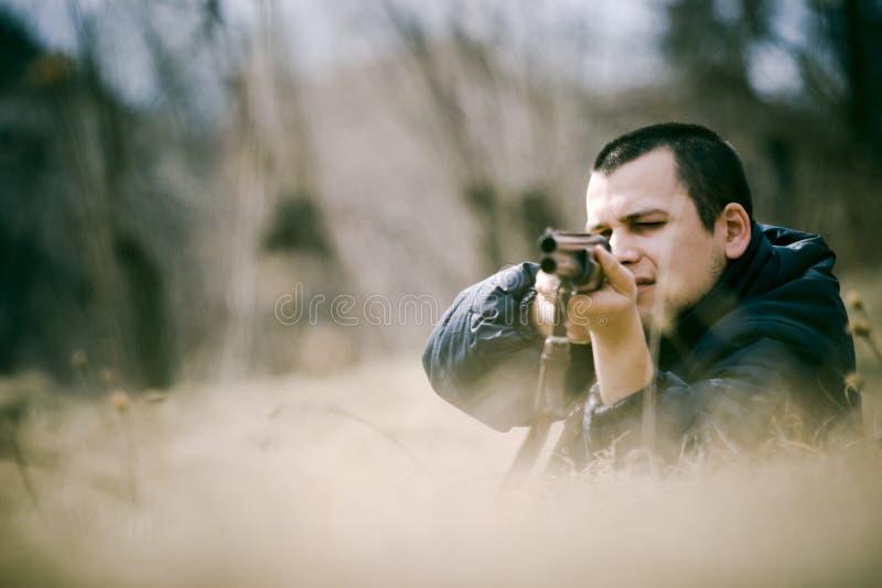 Hunter Aiming Gun. Crouching hunter aiming a shotgun stock photography