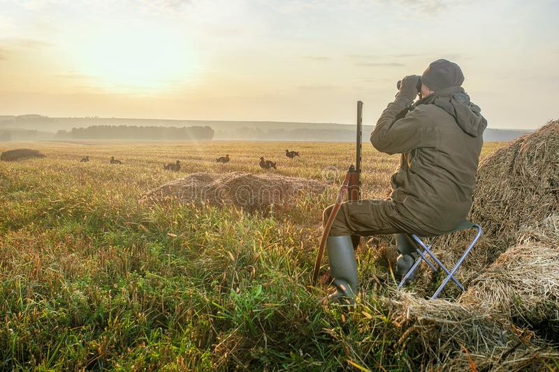 Hunter with a binoculars and a hunting gun in the autumn. royalty free stock photography