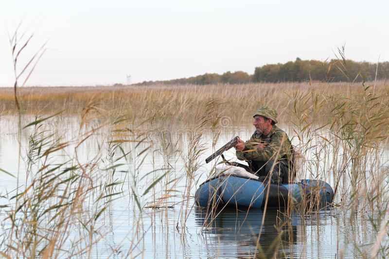 Download Hunter in a boat stock photo. Image of camouflage, season - 26974010