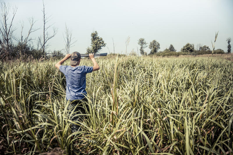 Hunter boy breakthrough tall grass during hunting season in summer day with copy space stock photography