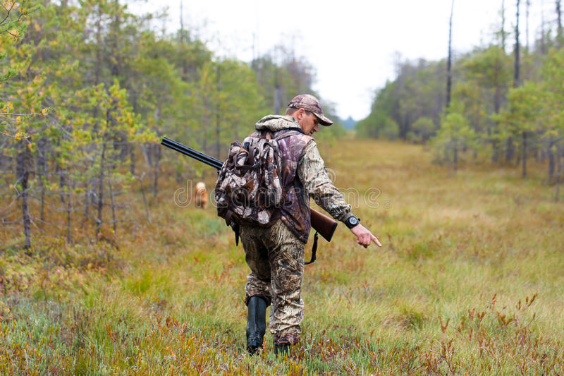 Hunter in camouflage on autumn hunting stock photo