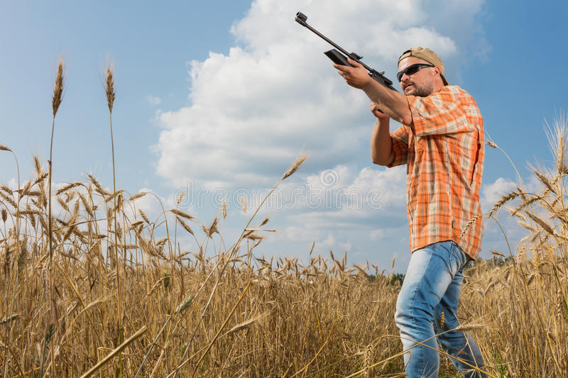 Hunter in cap and sunglasses aiming a gun at field stock images