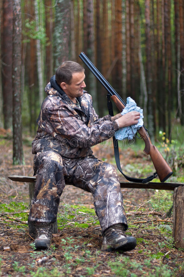 Hunter cleaning shotgun in the forest camp stock photos