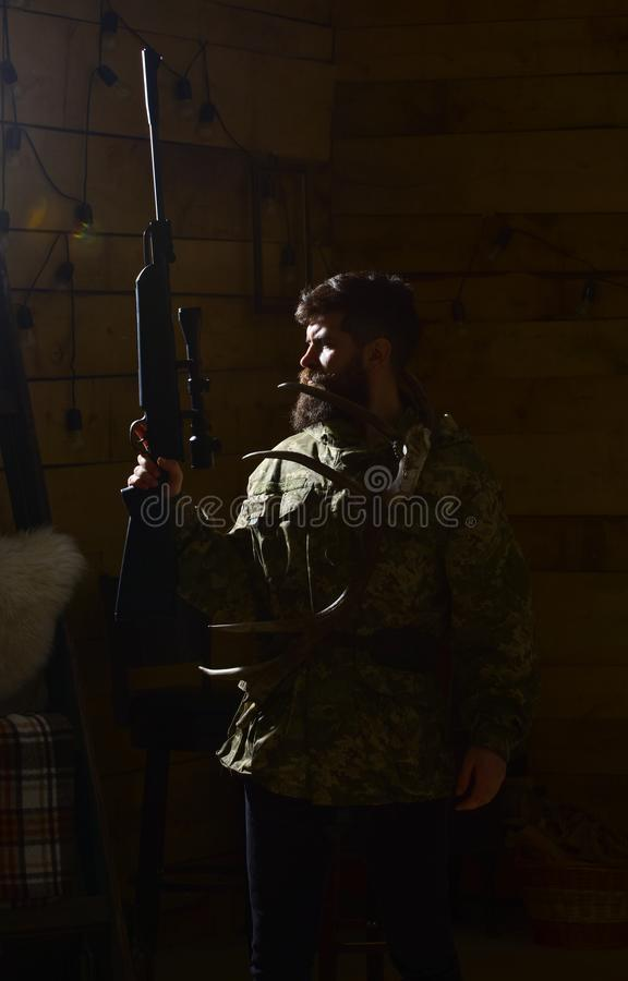 Hunter concept. Man with beard wears camouflage clothing, dark background. Macho on strict face at gamekeepers house stock photo
