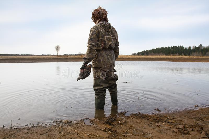 Hunter with a duck decoy in his hand stands on the shore. Duck hunter with a duck decoy in his hand stands on the shallow water royalty free stock images