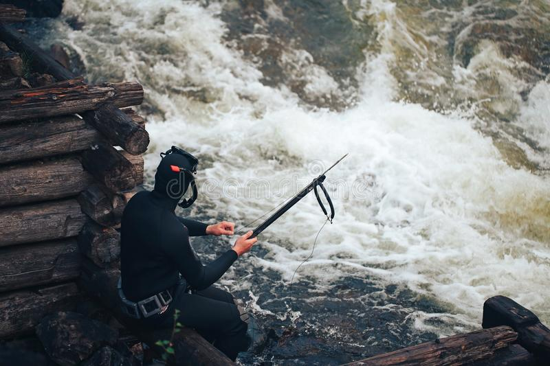 Hunter Fisherman Charges a Speargun. Hunter Fisherman in Wetsuit Charges a Speargun in Preparation for a Hunt stock image