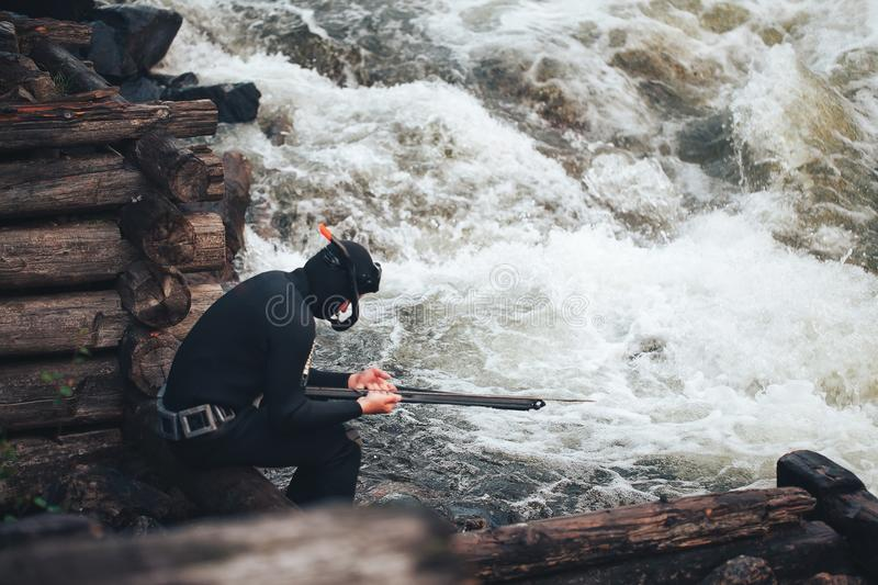 Hunter Fisherman Charges a Speargun. Hunter Fisherman in Wetsuit Charges a Speargun in Preparation for a Hunt stock photo