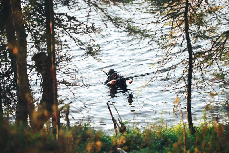 Hunter Fisherman is Hunting a Fish on the River. Hunter Fisherman in Wet Suit with a Speargun is Hunting a Fish on the River royalty free stock photography