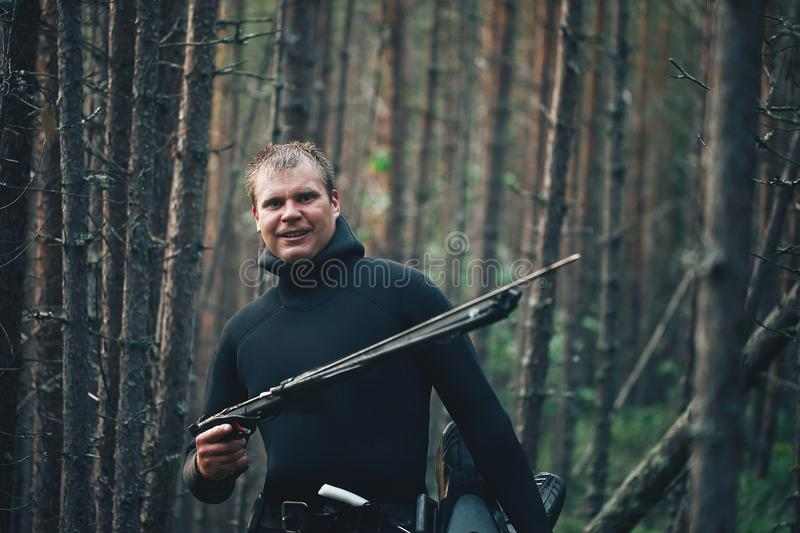 Hunter Fisherman is Posing on Forest River Coast. Hunter Fisherman in Wet Suit with a Speargun is Posing on Forest River Coast stock photos
