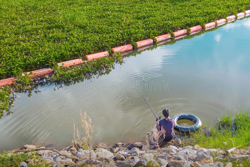Hunter fisherman with a speargun on a life ring looks under the water in search of fish stock image