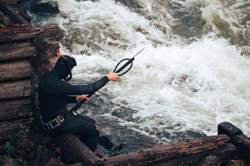 Hunter Fisherman Charges a Speargun. Hunter Fisherman in Wetsuit Charges a Speargun in Preparation for a Hunt stock images