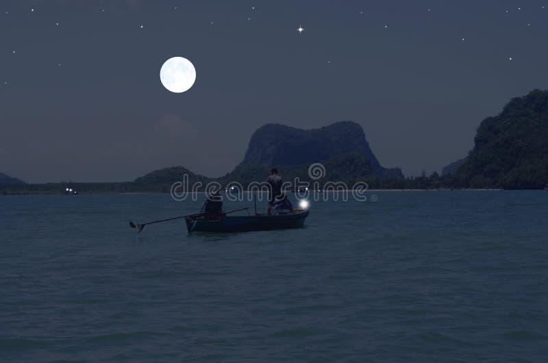 Hunter fishermen in boat under full moon light stock photo