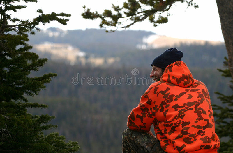 The Hunter Guy. A smiling hunter wearing orange camouflage and a blue knit beenie cap overlooks a deep valley below. Could also be used to show an outdoor stock photo