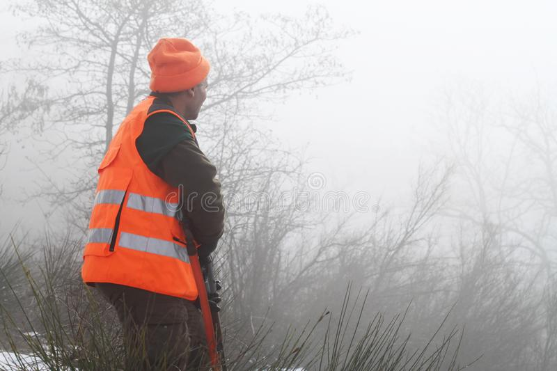Hunter with high visibility clothing and rifle, waiting for boar hunting in foggy countryside. Hunt concept stock images