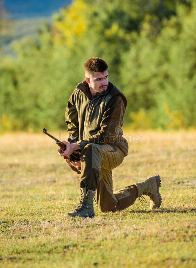 Hunter khaki clothes ready to hunt hold gun mountains background. Hunting shooting trophy. Hunter with rifle looking for stock photos