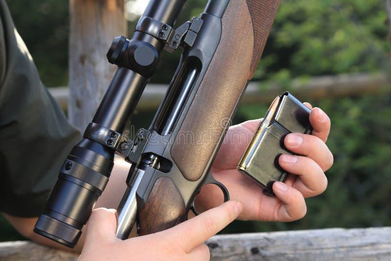 Hunter loading his hunting rifle gun with magazine stock photography