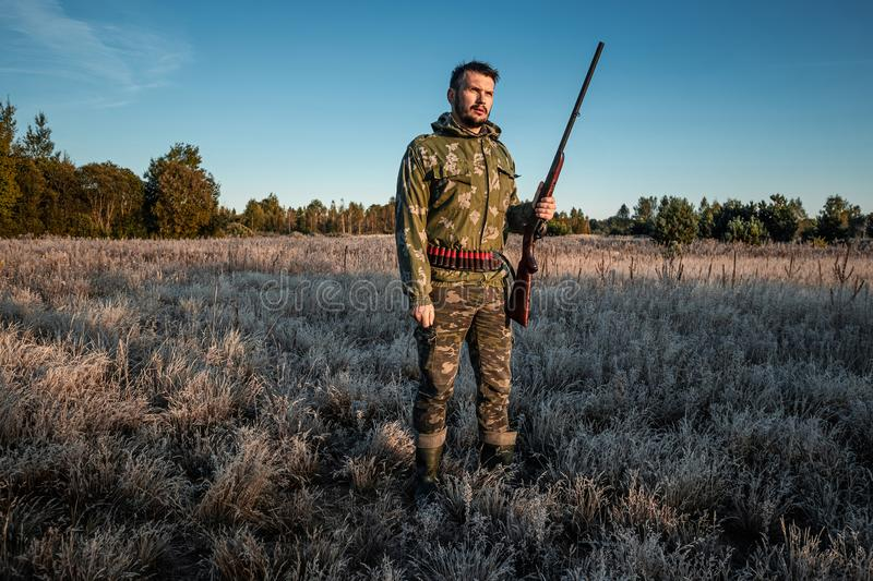 Hunter man in camouflage with a gun during the hunt in search of wild birds or game on the background of the autumn forest. Autumn royalty free stock images